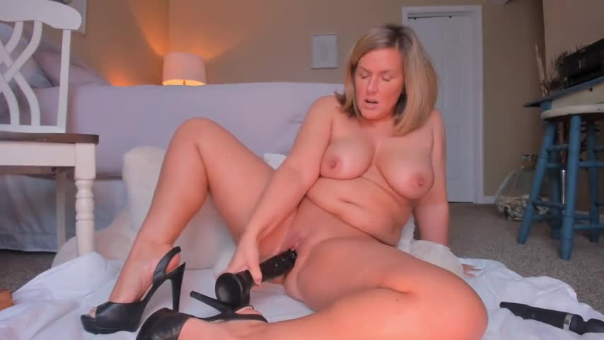 Fat mature lady sticking a big black dildo in her pussy